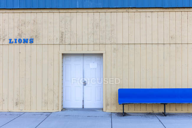 Lions Club building with the door closed and an empty blue bench outside. — Fotografia de Stock