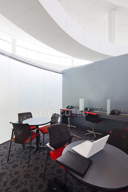 A business centre, tables and chairs, laptops and telephones. — Stock Photo