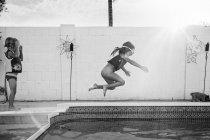 Девочка прыгает в бассейн — стоковое фото