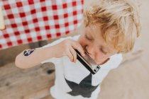 Blond garçon jouer un harmonica — Photo de stock