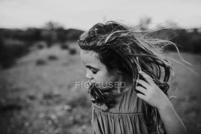 Vento soprando os cabelos de uma menina — Fotografia de Stock