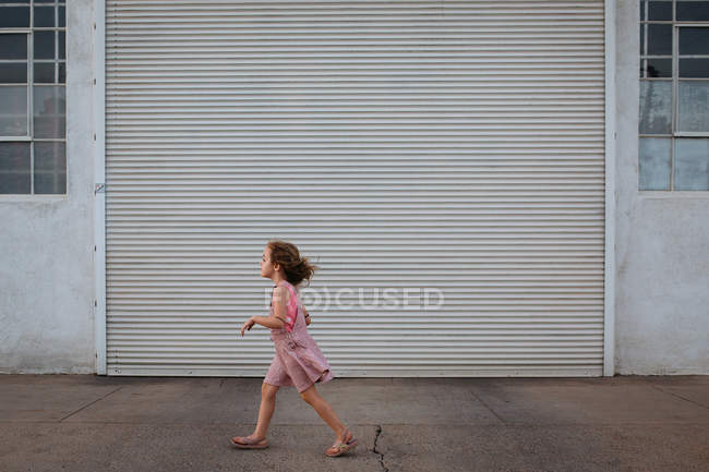 Girl in pink dress walking on the street — Stock Photo