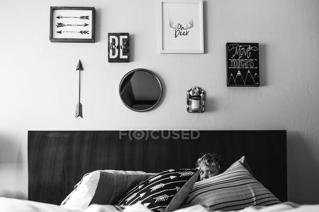 Cabeça de menino olhando para fora das almofadas — Fotografia de Stock