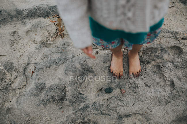 A girl's feet on a sandy beach — Stock Photo