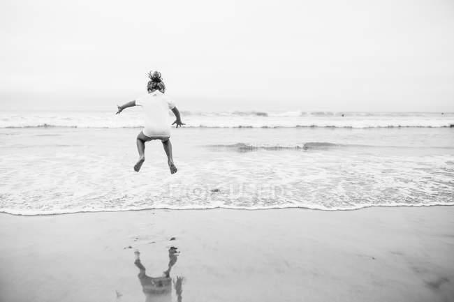 Chica feliz saltando en el mar - foto de stock