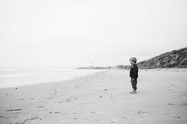 Boy looking at the sea on beach — Stock Photo