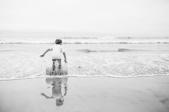 Счастливая девушка прыгает в море — стоковое фото