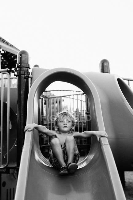 Хлопчик ковзання вниз на слайді — стокове фото