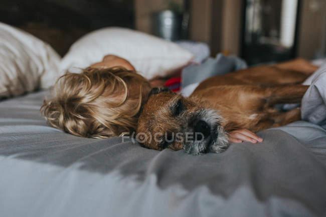Niño abrazándose en la cama con su perro - foto de stock