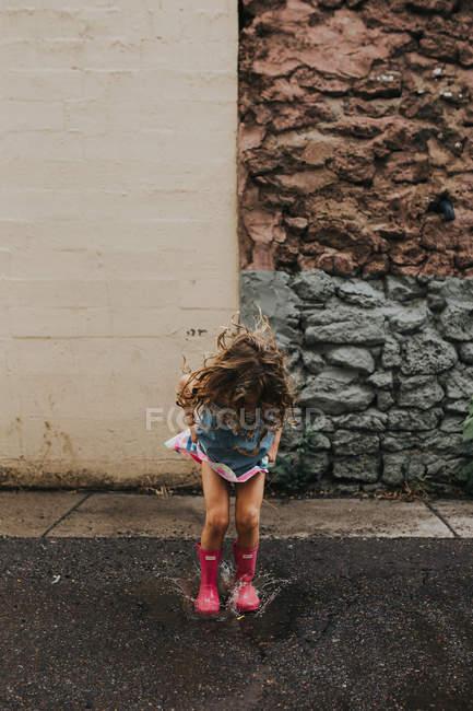 Girl jumping puddles on rainy street — Stock Photo