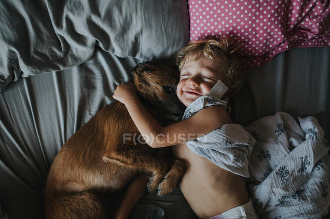 Junge umarmt seinen Hund im Bett — Stockfoto