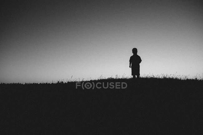 Silhouette of boy standing in field — Stock Photo