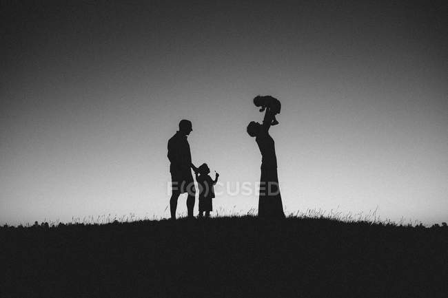 Family with children walking in field — Stock Photo