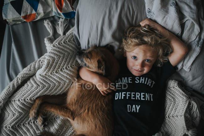 Menino deitado na cama com seu cachorro — Fotografia de Stock