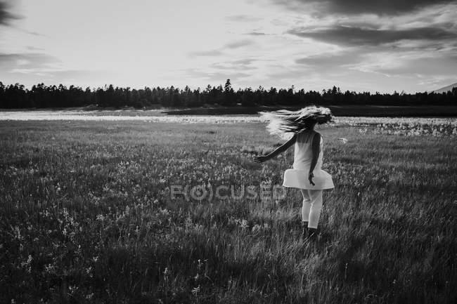 Девушка в белом платье прыгает по полю — стоковое фото