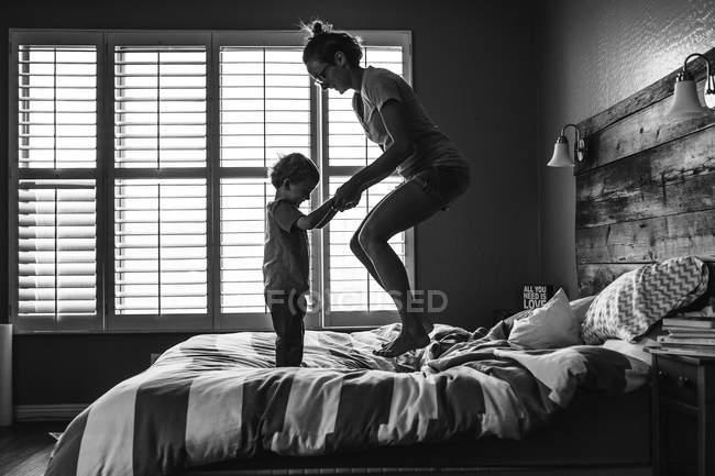 Mãe com o filho dela pulando juntos na cama — Fotografia de Stock