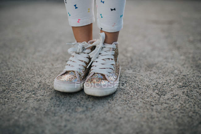 Female legs in colorful sparkling sneakers — Stock Photo