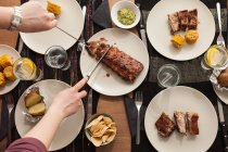 Table with grilled ribs, potatoes and corn — Stock Photo