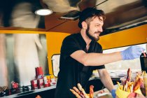 Hipster in hat selling food in food truck — Stock Photo