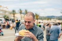 Смажені пиріжки людина їсть — стокове фото