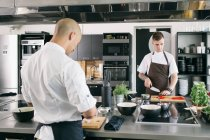 Chef and student cooking in kitchen — Stock Photo