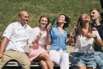 Друзі з шампанським, сидячи на відкритому повітрі — стокове фото
