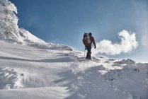 Людина, що похід по засніжених гір — стокове фото