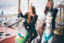 Hermosas mujeres divirtiéndose en carrusel - foto de stock