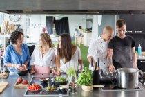 Amigos hablando y cocinando en la cocina - foto de stock