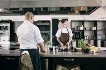 Шеф-кухар з студентом приготування їжі на кухні — стокове фото