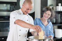Chef teaching woman to cook soup — Stock Photo