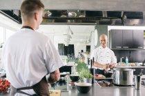 Mann auf der Suche an lächelnd Chef in der Küche — Stockfoto