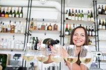 Happy girl pouring wine in glasses — Stock Photo