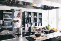 Cocinero profesional preparando comida en cocina - foto de stock
