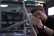 Craftsman taking measurements of bars — Stock Photo