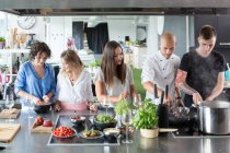 Friends talking and cooking in kitchen — Stock Photo