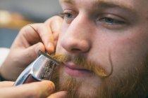 Barber arranging moustache — Stock Photo