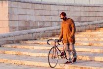 Людина прогулянки вниз по сходах з велосипеда — стокове фото