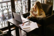 Blonde woman writing in planner in cafe — Stock Photo