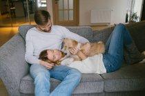 Chien caressant couple sur canapé — Photo de stock