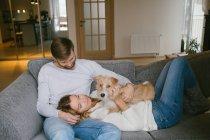 Couple stroking dog on sofa — Stock Photo