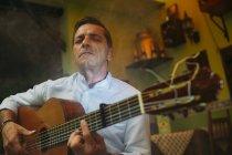 Portrait of elderly man playing guitar — Stock Photo