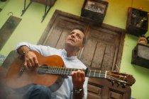 Porträt eines älteren Mannes, der Gitarre spielt — Stockfoto