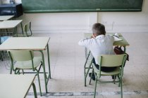 Schoolboy at desk in classroom — Stock Photo