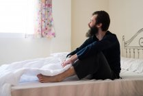 Bärtiger Mann sitzen im Bett — Stockfoto