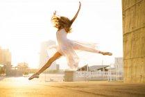Seitenansicht der junge Balletttänzerin Ballett im Geschaeftsviertel durchführen — Stockfoto