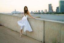 Brunette ballerina girl leaning on stone handrail and looking aside — Stock Photo