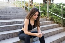 Sportive young woman sitting on stairs and listening to music. — Stock Photo