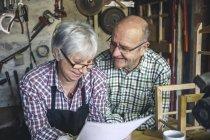 Portrait of senior couple reading papers at workbench — Stock Photo