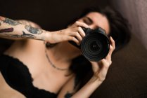 Pretty woman lying and holding camera — Stock Photo